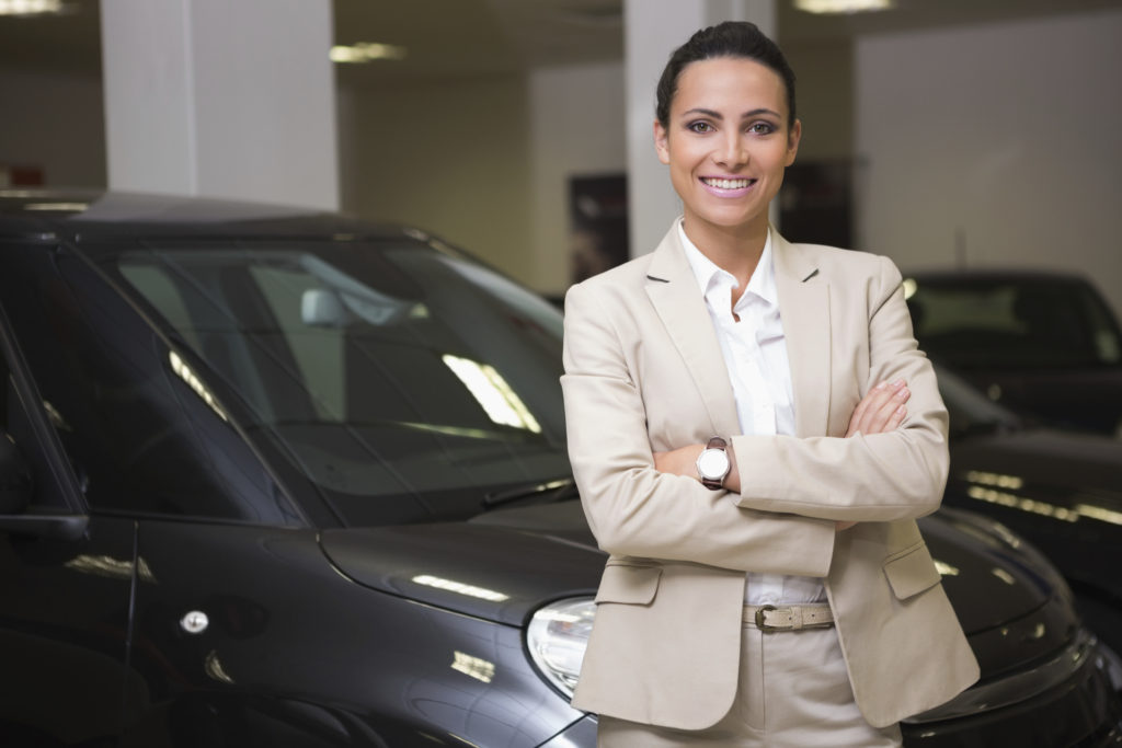 Smiling businesswoman standing with arms crossed at new car showroom