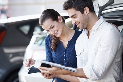 Positive couple smiling and browsing a catalogue in a car dealership
